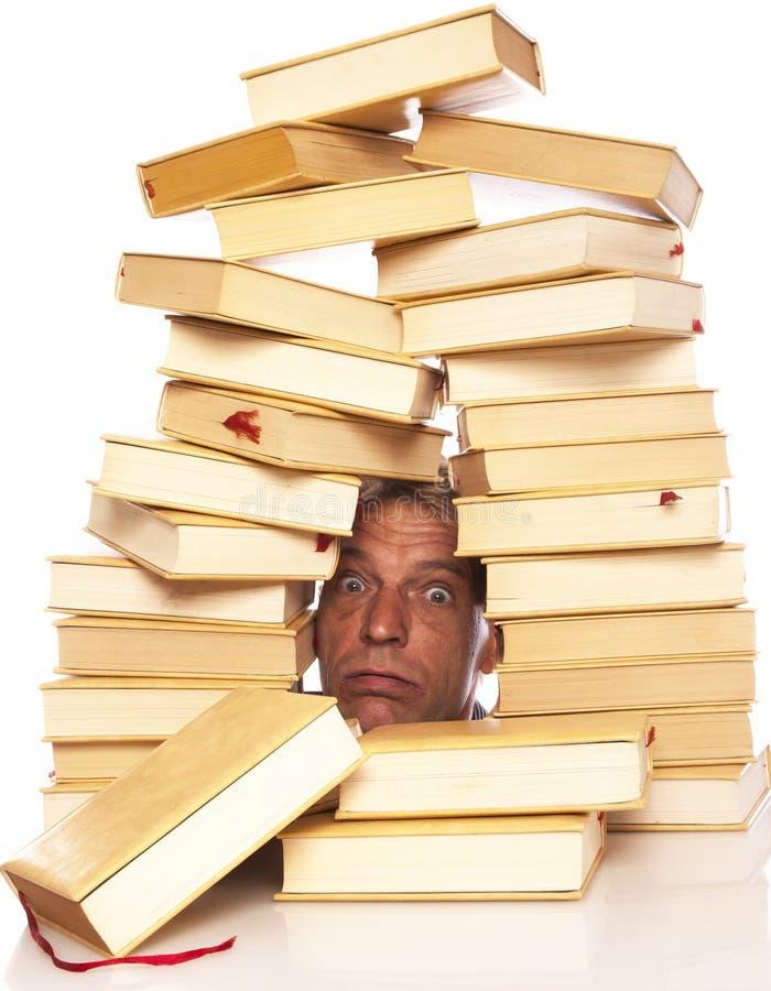 Mężczyzna z głową między książkami na białym tle obraz royalty free