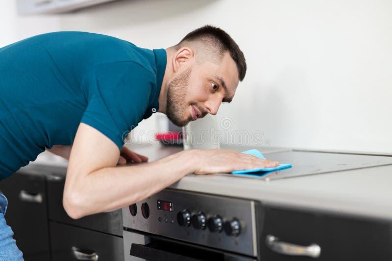 Mężczyzna z gałganianą cleaning kuchenki kuchnią w domu obrazy stock