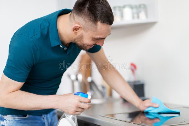 Mężczyzna z gałganianą cleaning kuchenki kuchnią w domu obraz stock