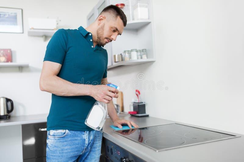 Mężczyzna z gałganianą cleaning kuchenki kuchnią w domu zdjęcia royalty free