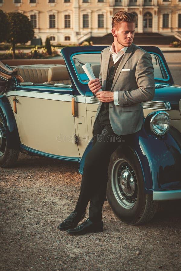 Mężczyzna z gazetowym pobliskim klasycznym kabrioletem zdjęcie royalty free
