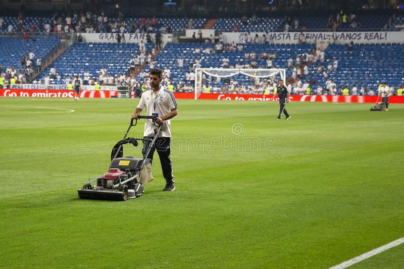 Mężczyzna z gazonu kosiarza tnącą trawą na boisku piłkarskim na S fotografia royalty free