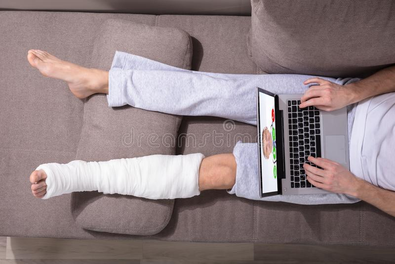 Mężczyzna Z Gipsującą nogą Używać laptop obraz royalty free