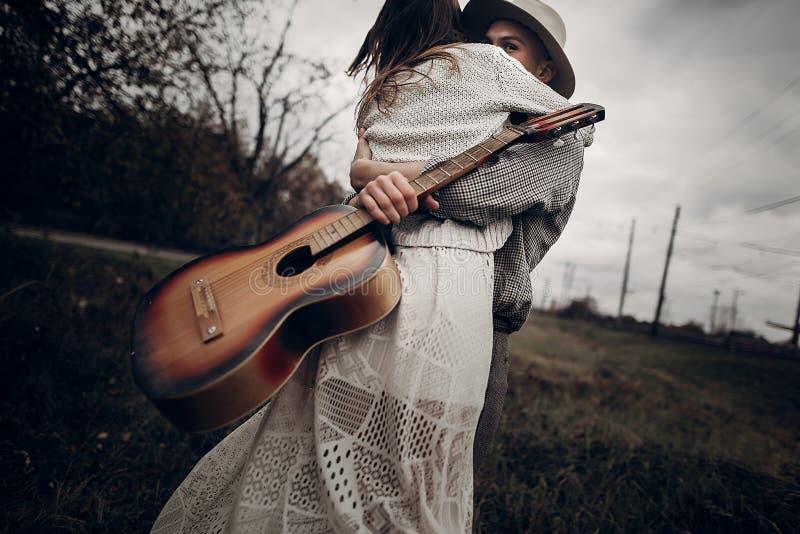 Mężczyzna z gitara tanem z jego boho gypsy kobietą w wietrznym polu obrazy royalty free