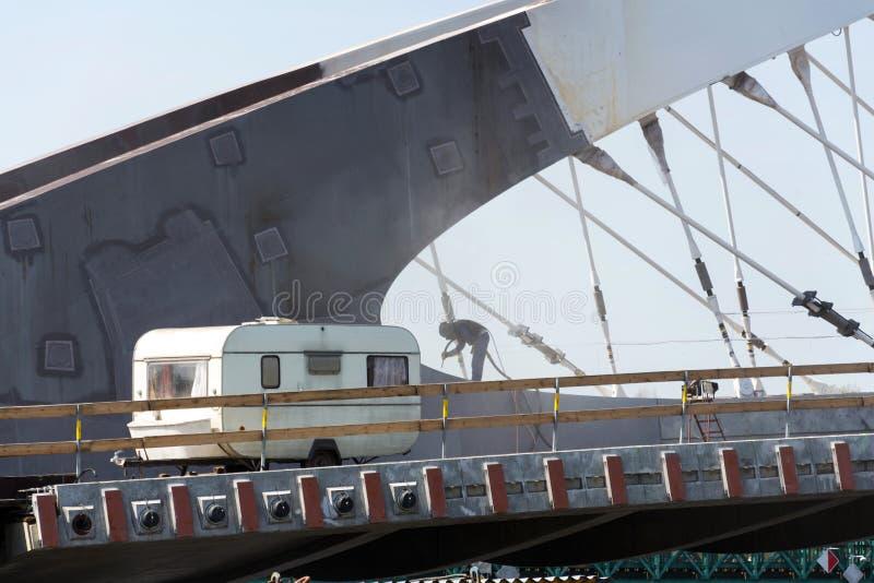 Mężczyzna z hełmem jak robot pracuje na bridżowej budowie z podróży przyczepą w przedpolu, robotyki automatyzacji lub sezonowej p fotografia stock