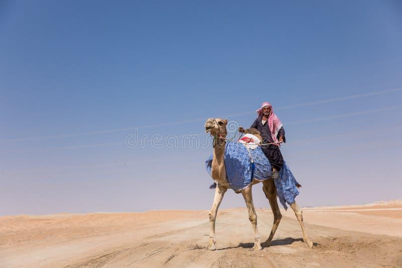 Mężczyzna z jego wielbłądem w pustyni zdjęcia royalty free