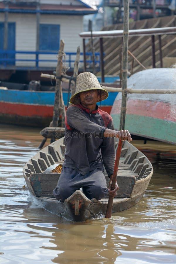 Mężczyzna z Kapeluszowej Wioślarskiej Tonle aproszy Jeziorną wioską rybacką Kambodża fotografia stock