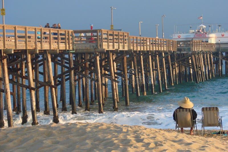 Mężczyzna z kapeluszowym obsiadaniem w plażowym krześle zdjęcie royalty free