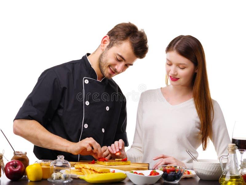 Mężczyzna z kobietą gotuje gofry w kuchni, mężczyzna stawia truskawki na gofrach zdjęcia royalty free
