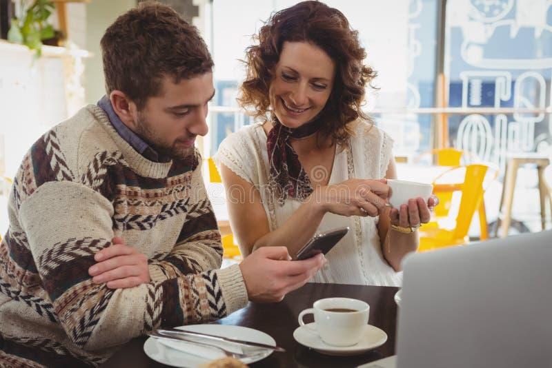Mężczyzna z kobietą używa telefon w kawiarni obraz stock