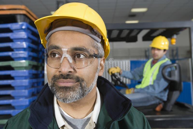 Mężczyzna Z kolegą Behind W fabryce fotografia royalty free
