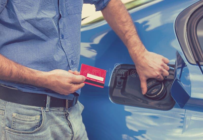 Mężczyzna z kredytową kartą otwiera paliwowego zbiornika nowy samochód zdjęcie royalty free