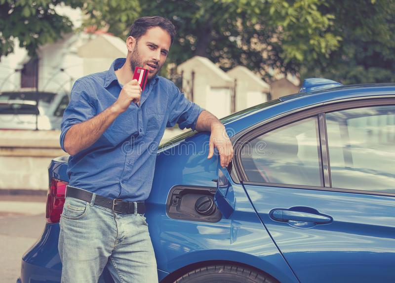 Mężczyzna z kredytową kartą otwiera paliwowego zbiornika nowy samochód zdjęcie stock