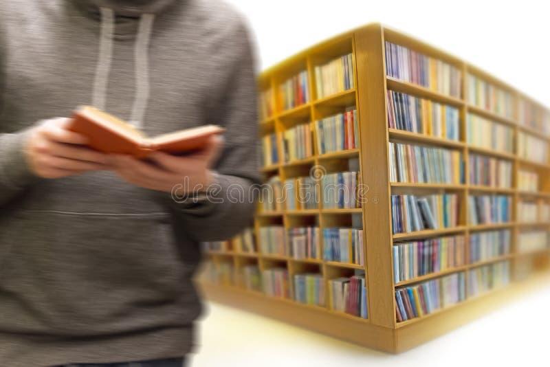 Mężczyzna z książką w bibliotece zdjęcia stock