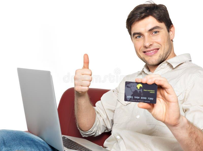 Mężczyzna z laptopem pokazuje kredytową kartę obrazy royalty free