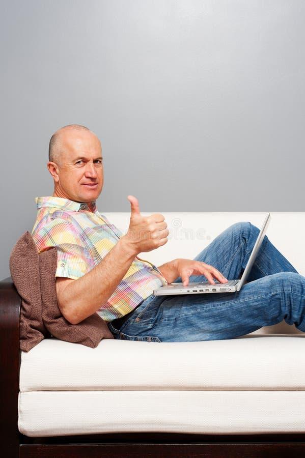 Mężczyzna z laptopem w domu pokazywać aprobaty fotografia stock