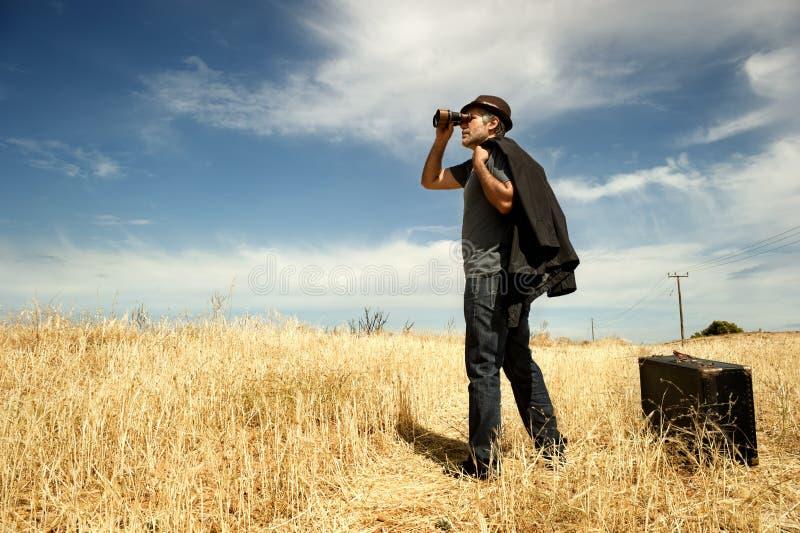 Mężczyzna z lornetkami w polu obrazy stock