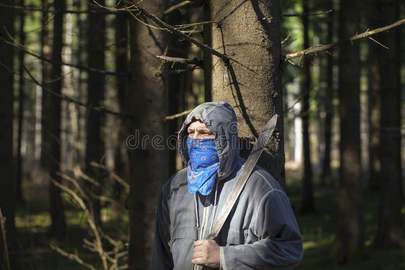 Mężczyzna z maczetą w drewnach zdjęcie stock