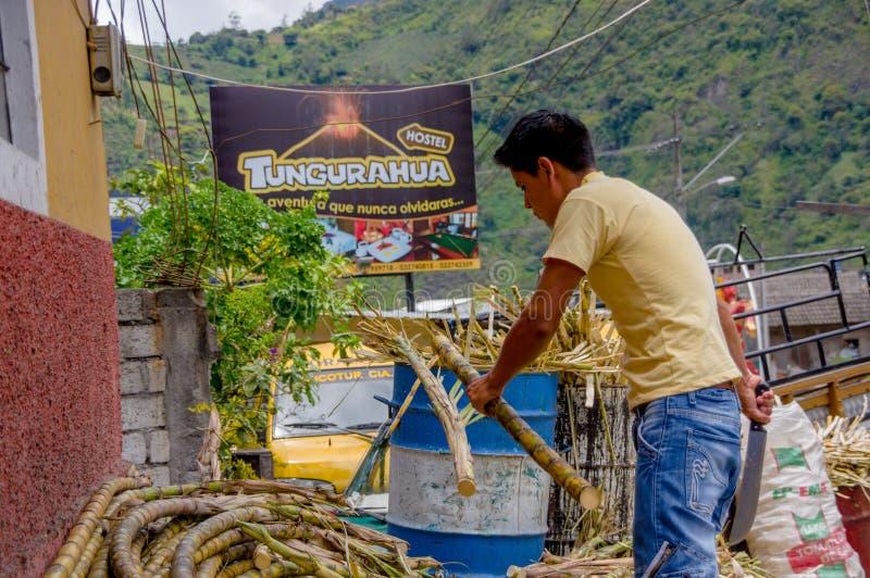 Mężczyzna z maczety ciapania trzcinami cukrowa w typowej Ekwadorskiej powabnej miasto ulicie obraz stock
