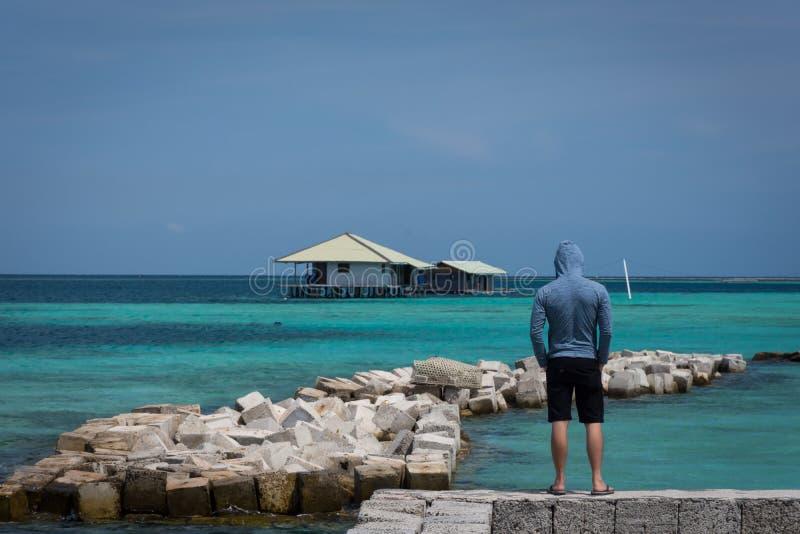 Mężczyzna z marynarki wojennej kurtką, krótkimi spodniami i patrzeje spławowy dom i rozpraszający kamienie z pięknym turkusowym o fotografia stock