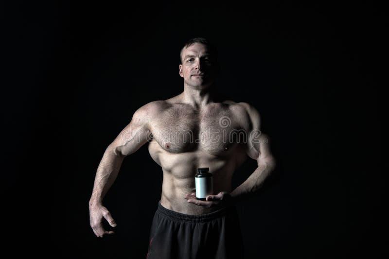 Mężczyzna z mięśniowego ciała chwyta pigułki słojem, sport obraz stock