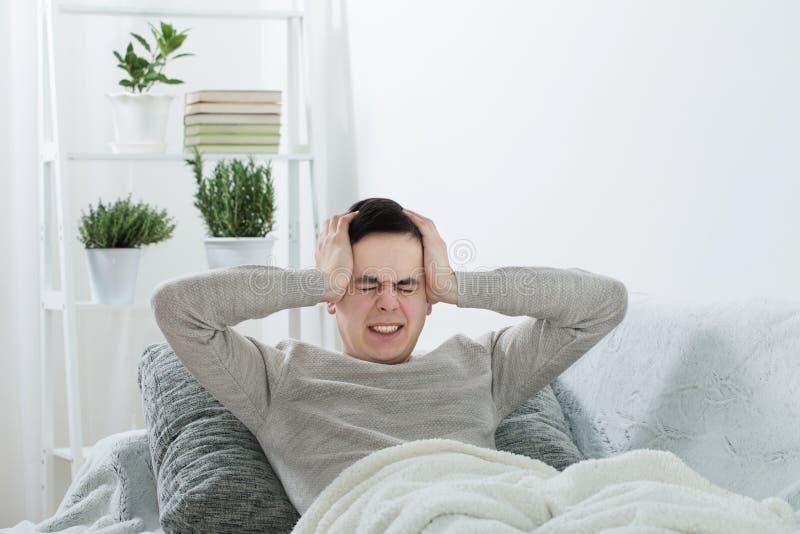 mężczyzna z migreną na kanapie zdjęcia stock