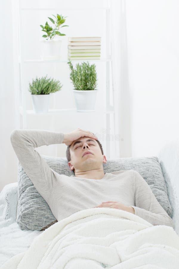 mężczyzna z migreną na kanapie zdjęcie royalty free
