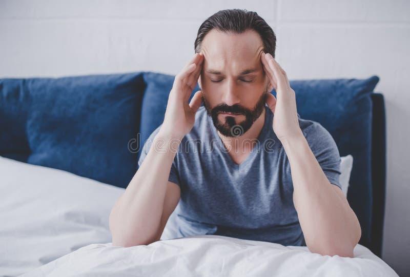 Mężczyzna z migreny obsiadaniem na łóżku zdjęcia royalty free