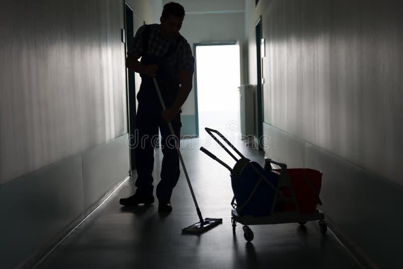 Mężczyzna z miotły cleaning biura korytarzem zdjęcia stock
