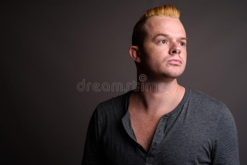 Mężczyzna z Mohawk blondynem przeciw szaremu tłu i fryzurą obrazy royalty free