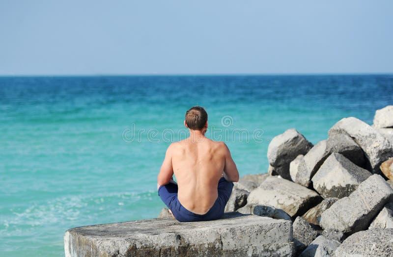 Mężczyzna z nagim półpostaci obsiadaniem na kamieniu z jej z powrotem patrzeć morze fotografia stock