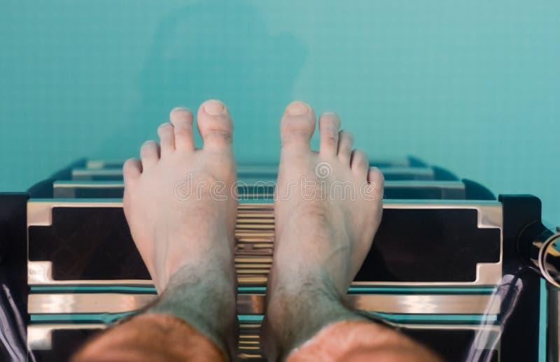 Mężczyzna z nagimi ciekami pochodzi na drabinie w basenie obraz royalty free