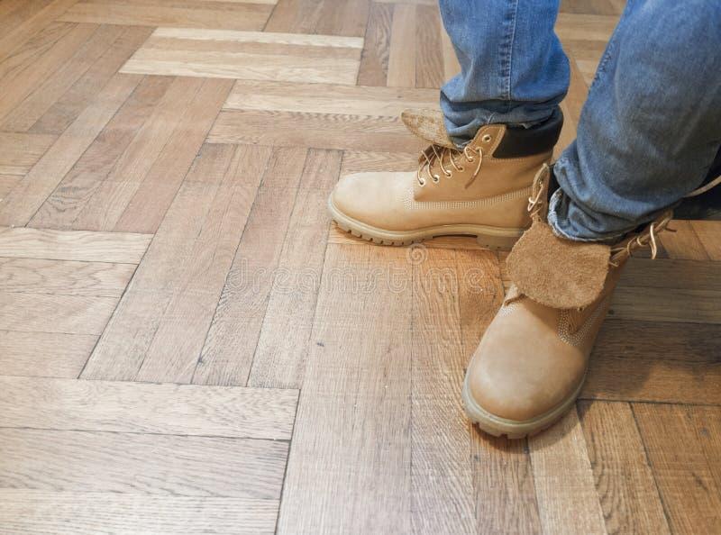 Mężczyzna z niebieskimi dżinsami i pracą inicjuje na drewnianej podłoga zdjęcia royalty free