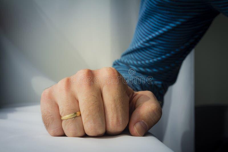 Mężczyzna z obrączką ślubną gniósł jego rękę na białym sukiennym backgro obrazy royalty free