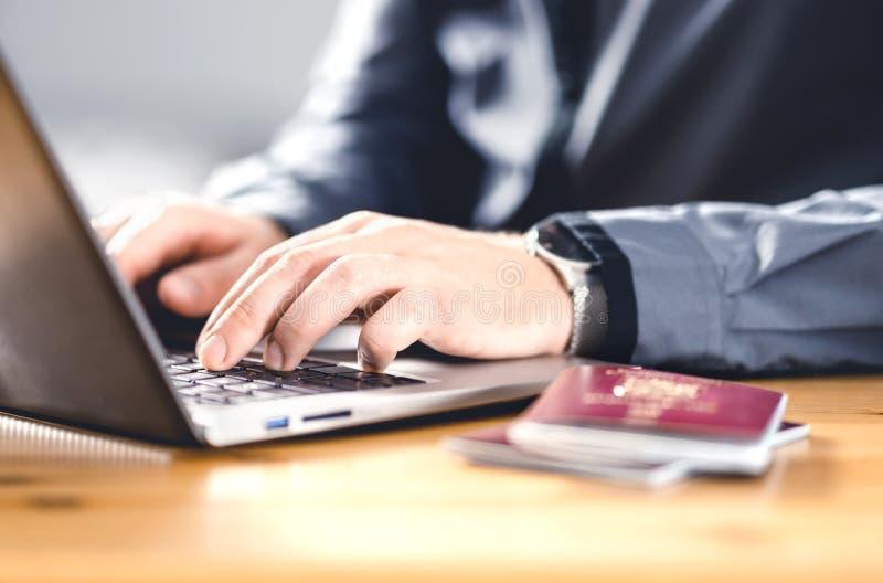 Mężczyzna z paszportem i laptopem Dokument podróży i identyfikacja Elektroniczny wniosek imigracyjny fotografia royalty free