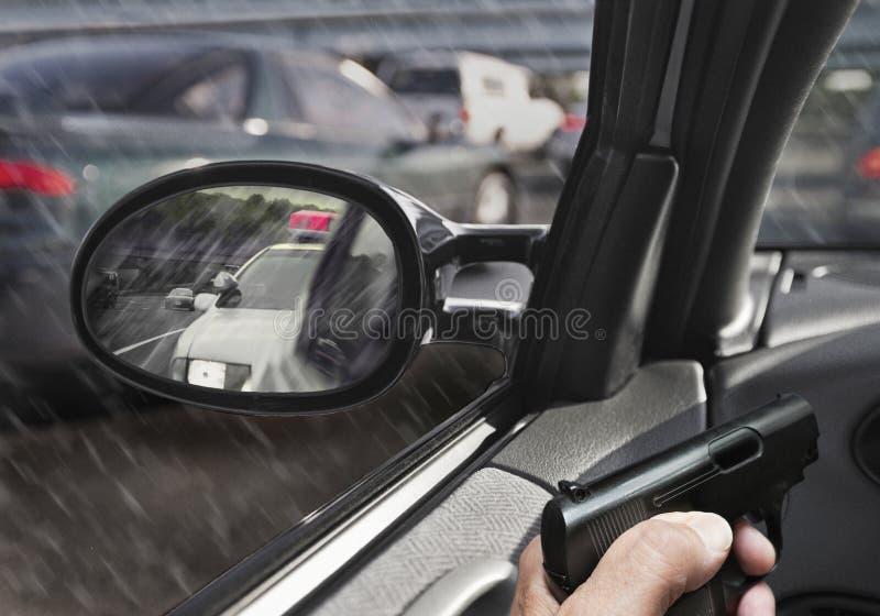 Mężczyzna z pistoletem w samochodzie z samochodem policyjnym w sideview lustrze obraz royalty free