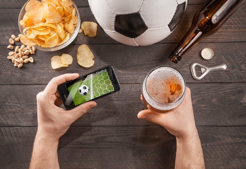 Mężczyzna z piwnym dopatrywanie meczem piłkarskim na smarphone fotografia royalty free