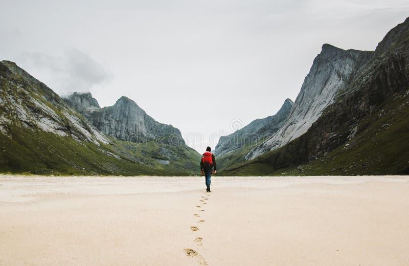 Mężczyzna z plecakiem chodzącym przy piaskowatą plażą daleko od samotnie obrazy royalty free