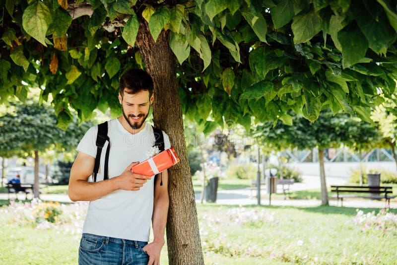 Mężczyzna z plecakiem i prezentem obok drzewa obraz stock