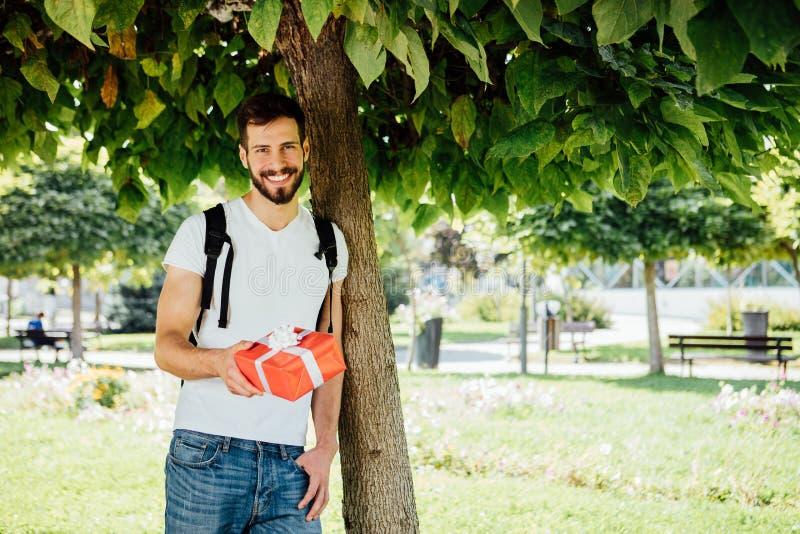 Mężczyzna z plecakiem i prezentem obok drzewa obrazy royalty free