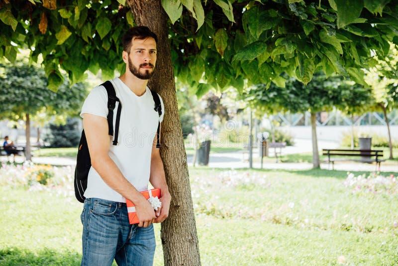 Mężczyzna z plecakiem i prezentem obok drzewa fotografia stock