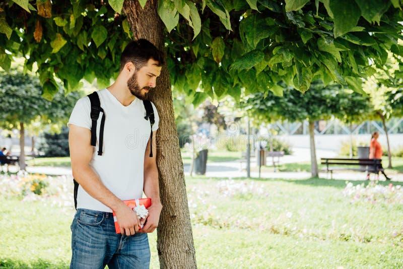 Mężczyzna z plecakiem i prezentem obok drzewa obraz royalty free