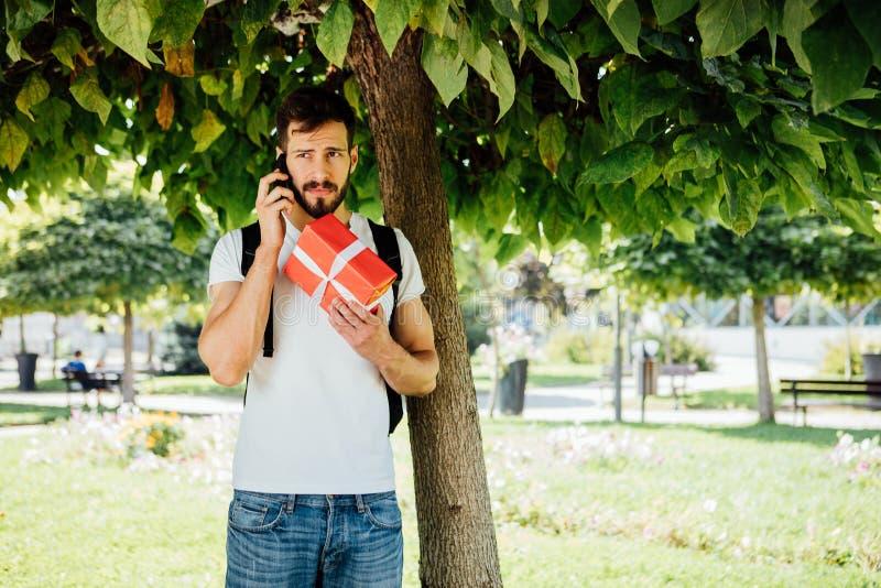 Mężczyzna z plecakiem i prezentem obok drzewa zdjęcie stock