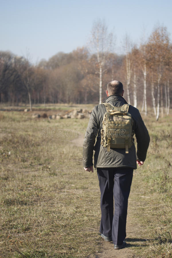 Mężczyzna z plecakiem na jego brać na swoje barki odprowadzenie na ścieżce w parku zdjęcie royalty free