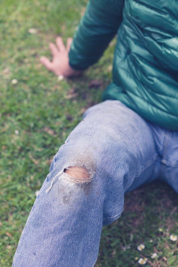 Mężczyzna z poszarpanymi cajgami na trawie zdjęcie royalty free