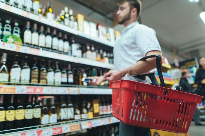 Mężczyzna z produktu kosza spojrzeniami przy supermarket półką i wybiera wino Mężczyzna robi zakupom w sklepie fotografia royalty free
