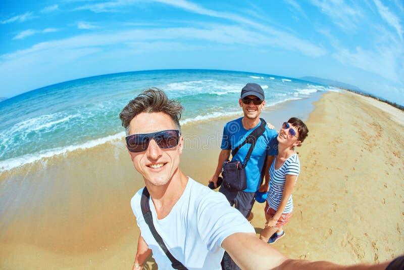 Mężczyzna z przyjaciółmi robi selfie na plaży obrazy royalty free