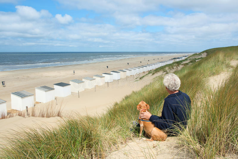 Mężczyzna z psem przy plażą obraz stock