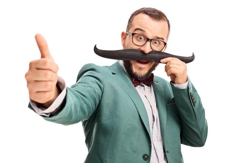 Mężczyzna z sfałszowanym wąsem daje kciukowi up zdjęcia royalty free