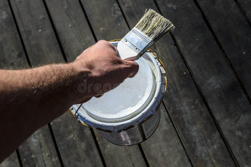 Mężczyzna z silną ręką niesie puszkę farba nad tarasem i trzyma muśnięcie, naprawa w intymnym domu, działanie malarza śliwki obraz stock